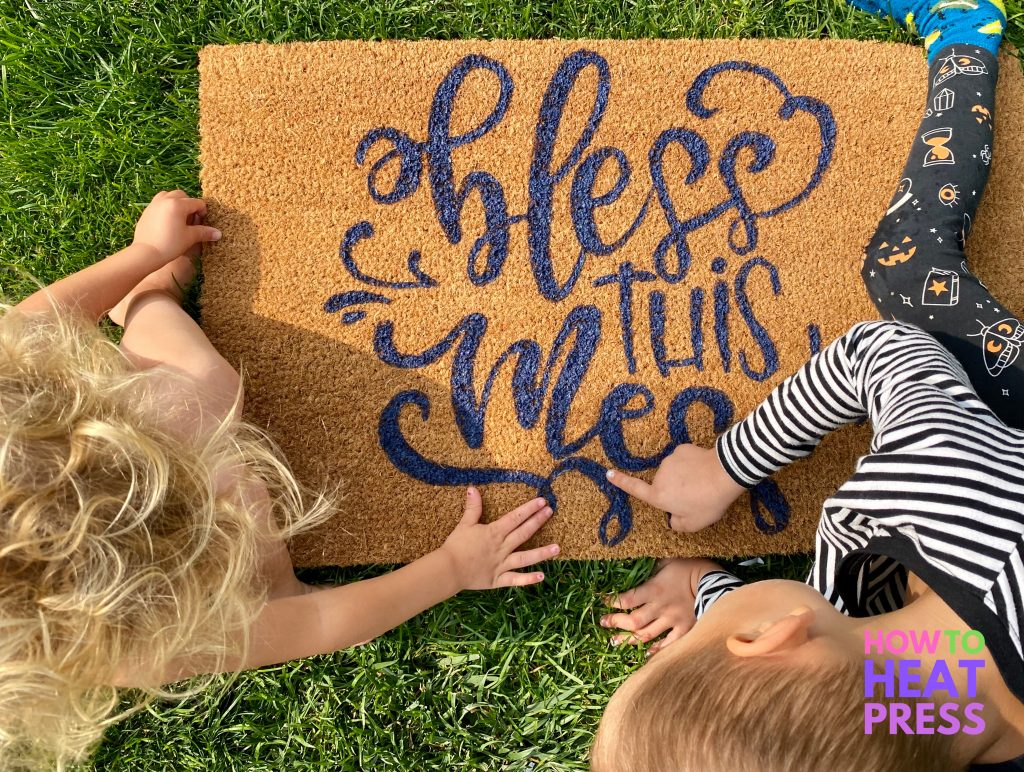 brown doormat with blue 'bless this mess' writing
