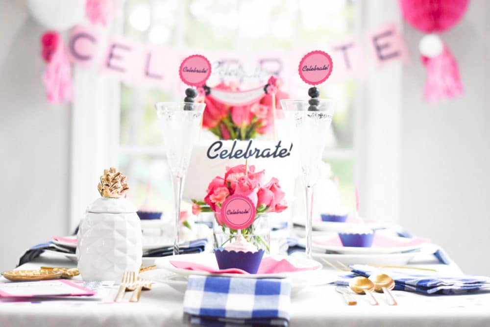 "table with pink, blue and white ""celebrate"" party decorations"