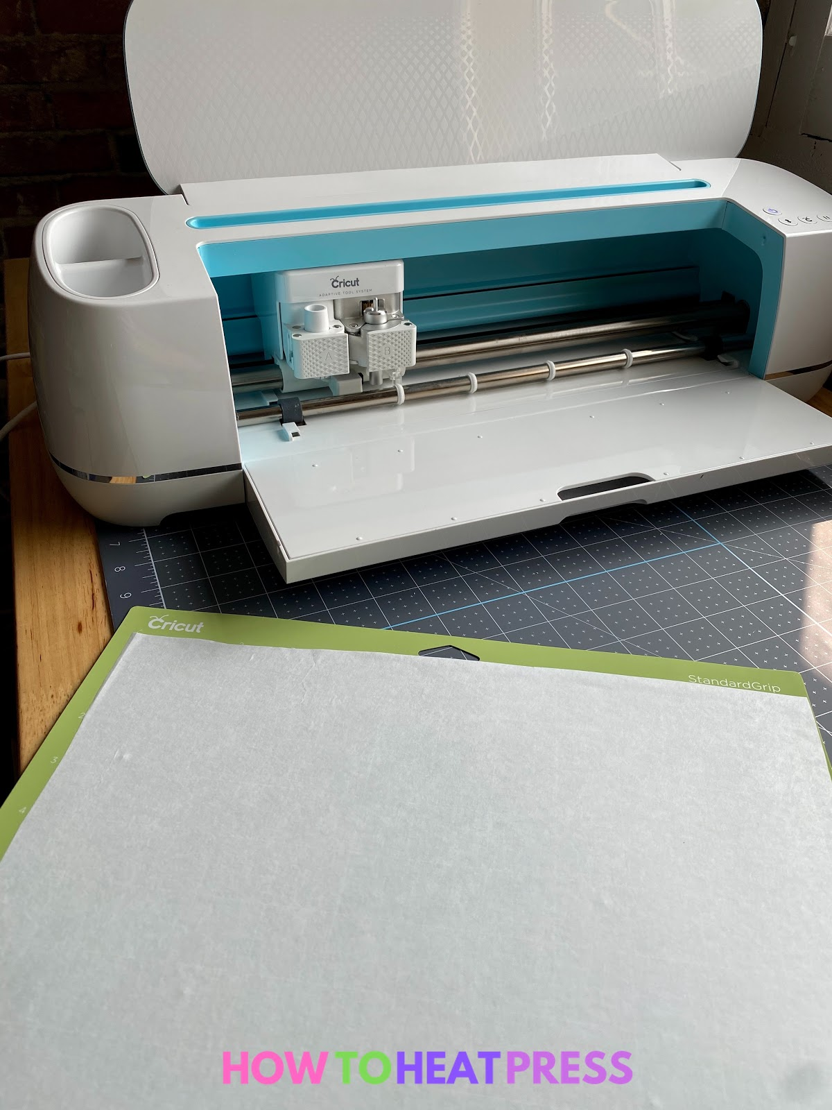freezer paper on cutting mat and blue cricut maker