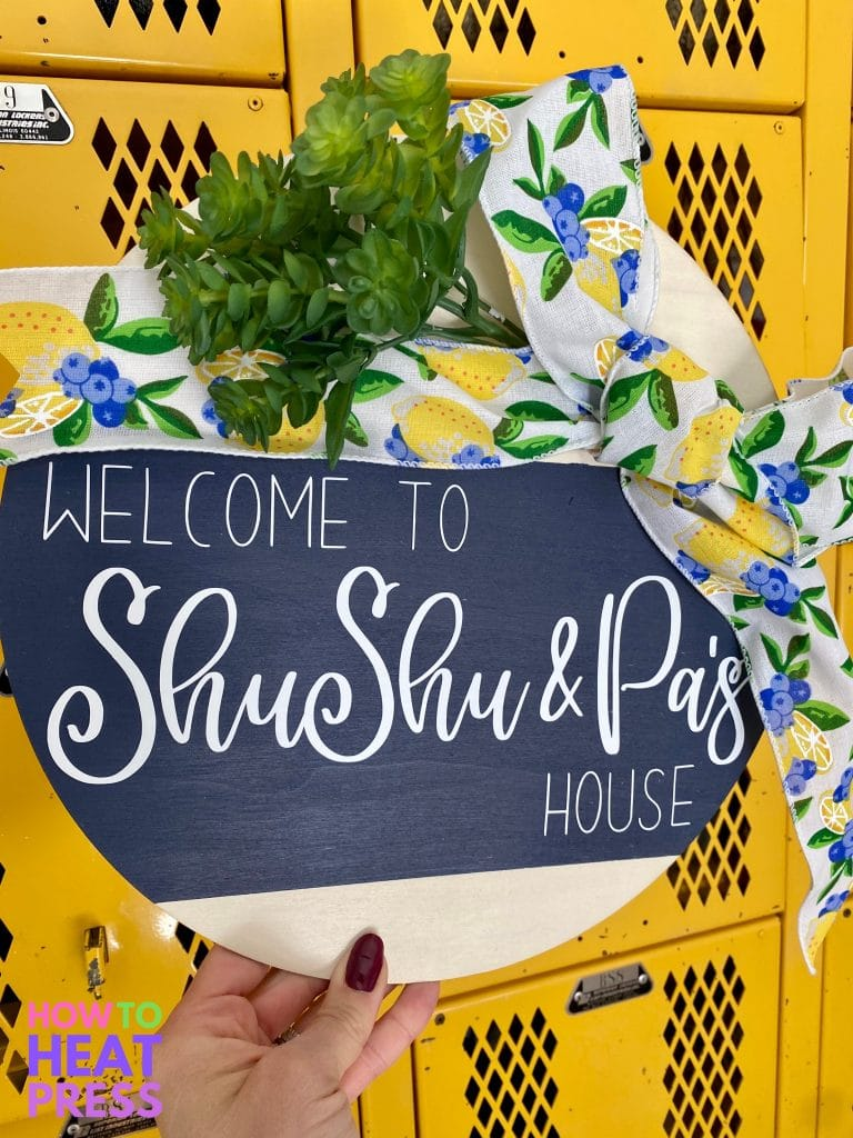 round wood sign with blue background, white letters, lemon and blueberry ribbon, and succulent