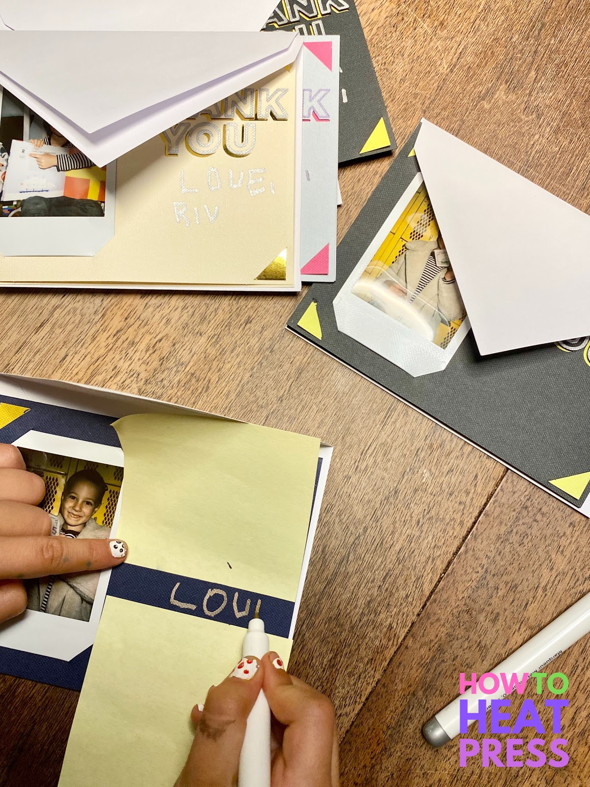 child writing 'love' on diy thank you cards with photos