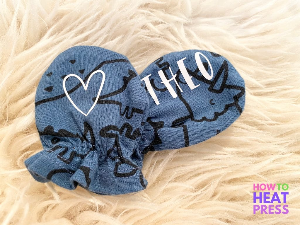 blue baby mittens with black dinosaurs and baby name and heart in white heat transfer vinyl