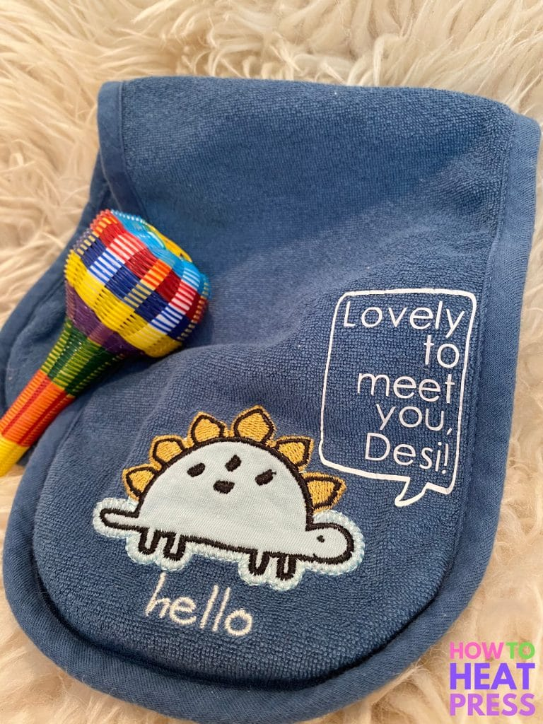blue burp cloth with dinosaur saying 'lovely to meet you, desi' in white htv