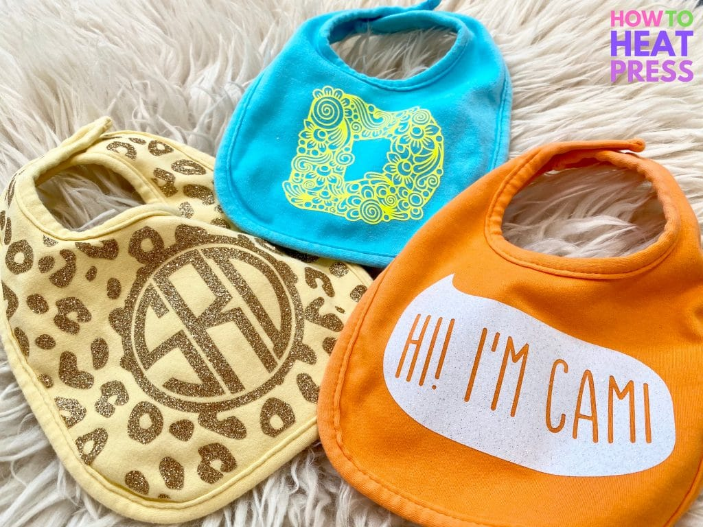 blue, yellow, and orange baby bibs customized with htv