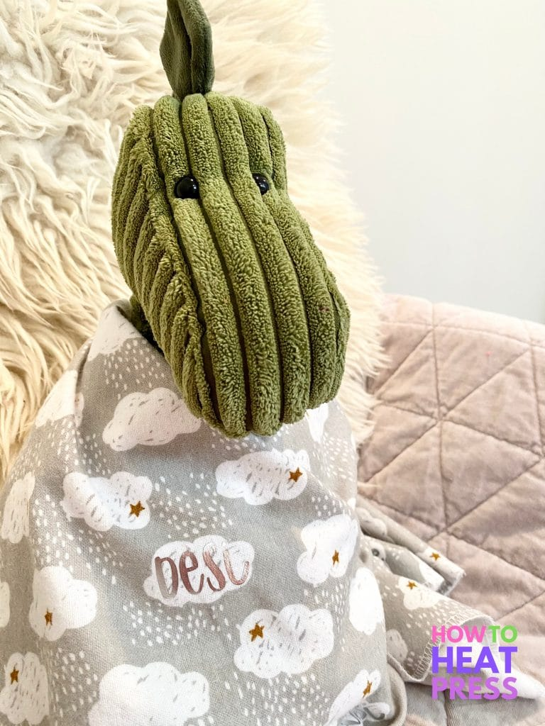 green dinosaur swaddled in gray baby blanket with clouds and baby name