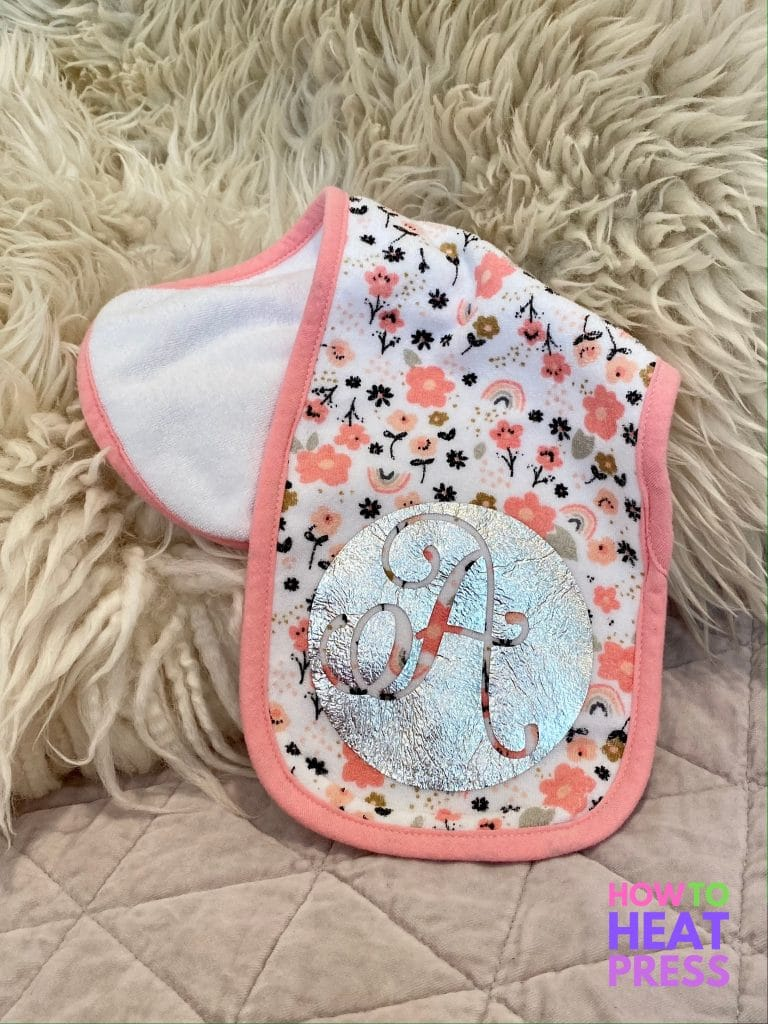 pink floral burp cloth with large cursive A cut out of silver foil htv