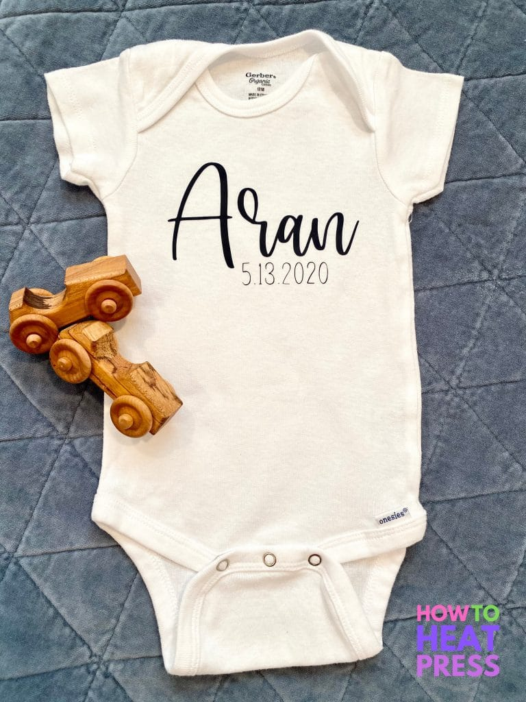 white gerber onesie with blue cursive name and date of birth