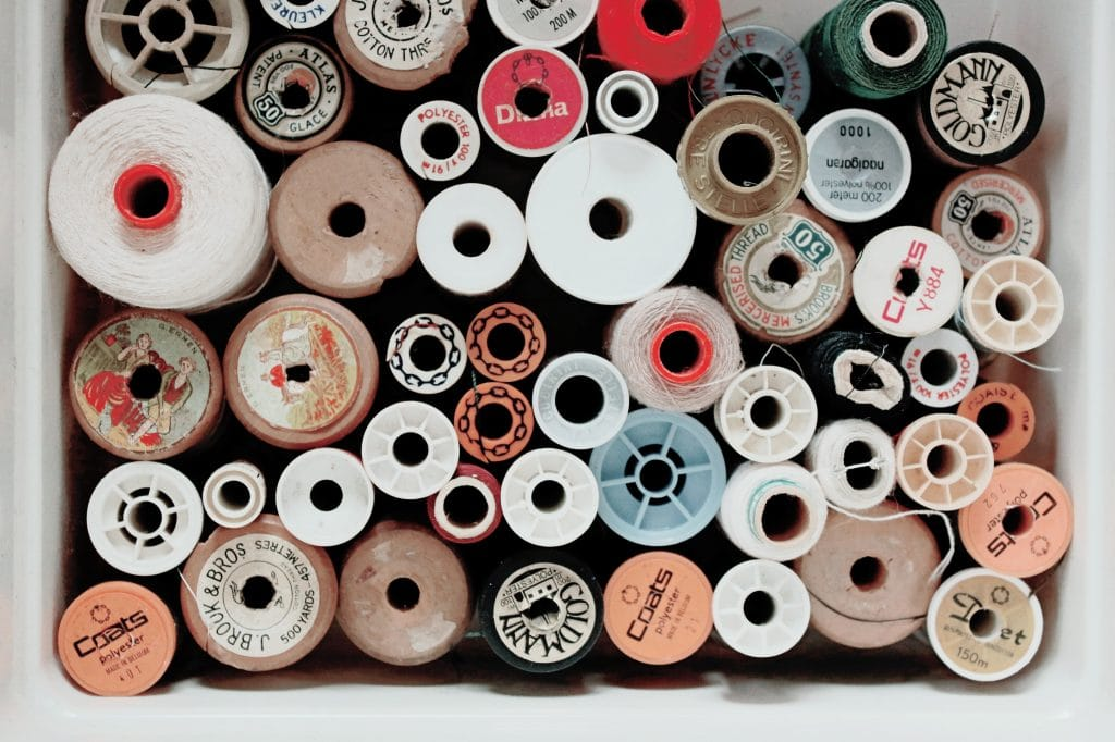 spools of thread in tan, red, and white