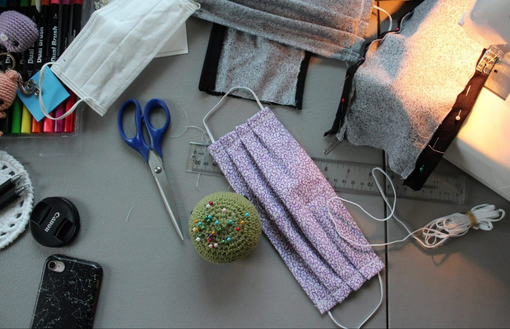 sewing machine, fabric, and scissors in work area making masks