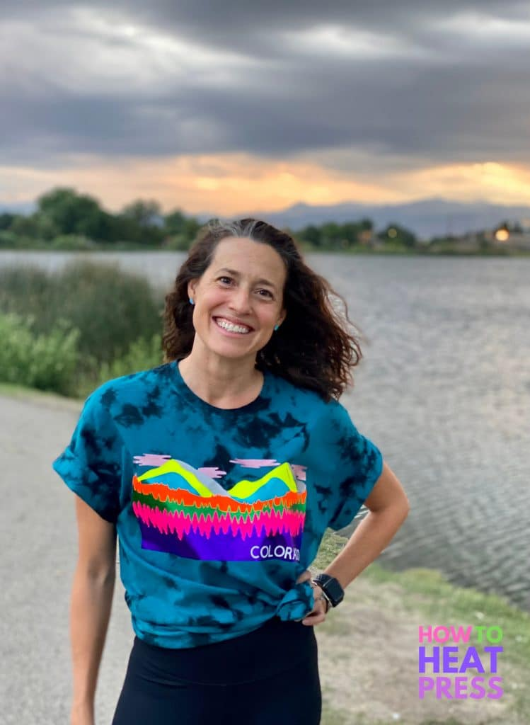 woman wearing shirt with layered htv design standing in front of mountains and lake