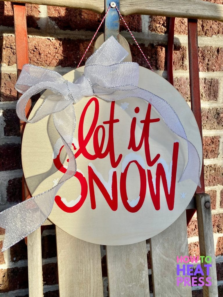 round wooden sign with red and white letters saying 'let it snow' with white and silver bow